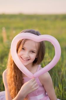 屋外のバルーンで幸せな美しい女の子