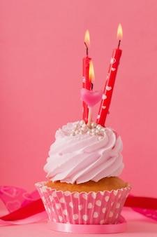 ピンクの背景にキャンドルとカップケーキ