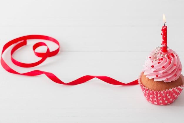 白い木製の背景にピンクのカップケーキ