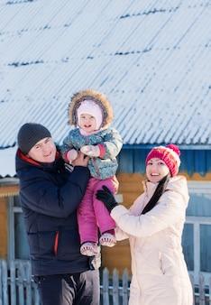 冬に彼の家の暖かい服立っている幸せな家族