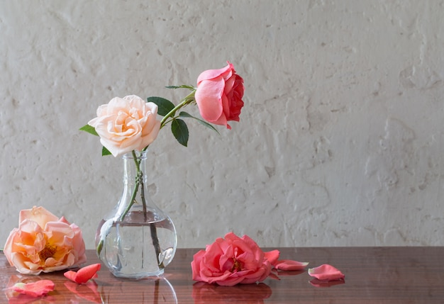 Розы в вазе на старом белом фоне