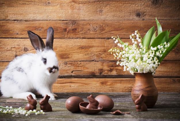 チョコレートの卵と木製の背景の花のウサギ