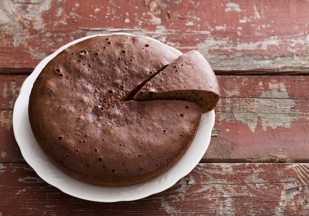 古い木製の背景にチョコレートスポンジケーキ