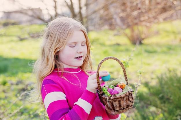 Счастливая девушка с пасхальными яйцами на открытом воздухе
