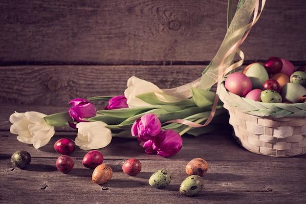 Тюльпаны и пасхальные яйца на деревянном фоне