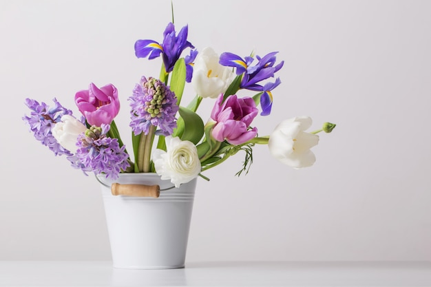 白い背景の上のバケツに春の花