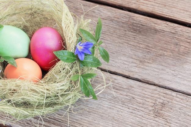Пасхальное яйцо гнездо с цветами на деревенском деревянном фоне