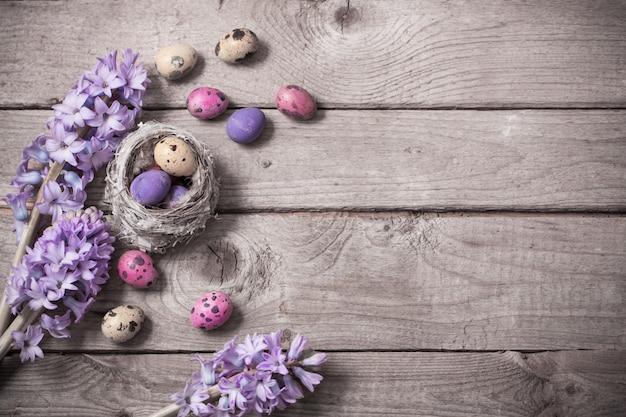 Пасхальные яйца с весенними цветами на деревянном фоне