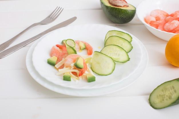Приготовленные креветки с авокадо и моцареллой на белом деревянном столе
