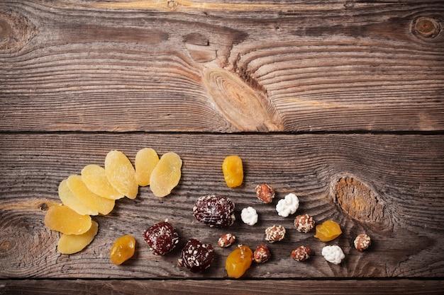 Смешайте орехи и сухофрукты на деревянном фоне