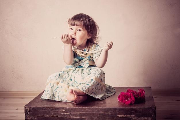 Маленькая девочка сидит на старом чемодане