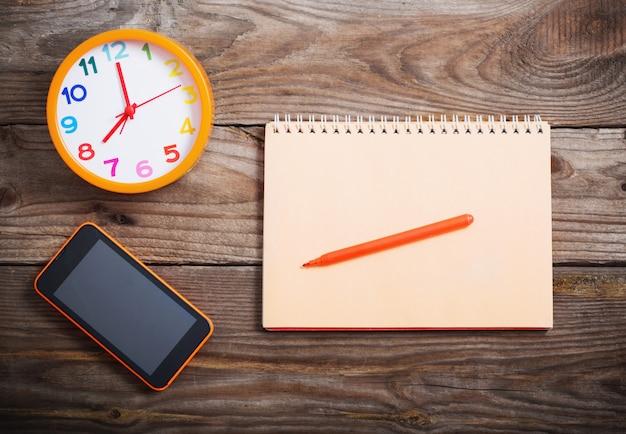 Смартфон, будильник и блокнот на деревянном фоне
