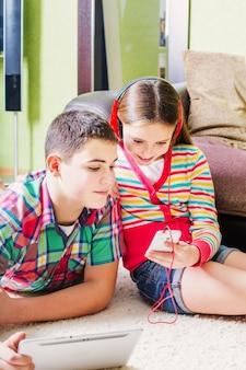 Дети с помощью электронного планшета и мобильного телефона