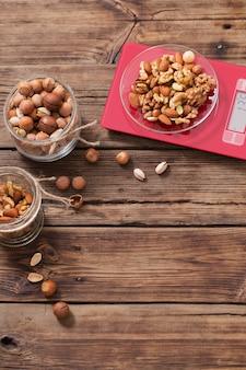 Смесь различных орехов на кухонные весы на старых деревянных фоне