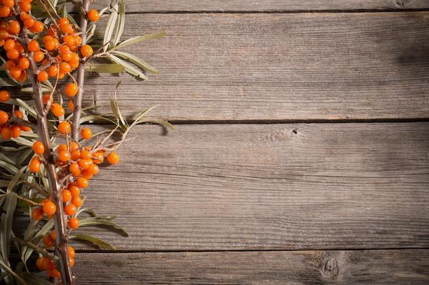 木製の背景に海クロウメモドキの果実