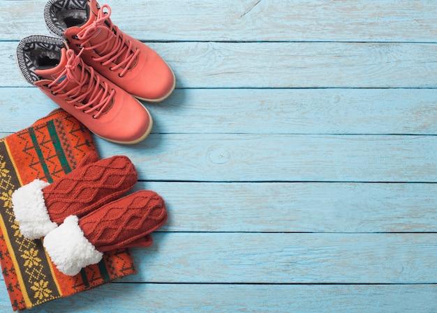 Зимняя одежда и обувь на деревянном фоне