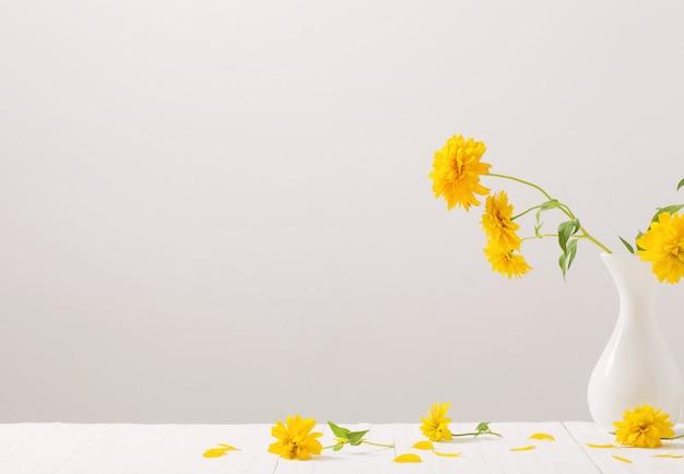 Желтые цветы в вазе на белой стене