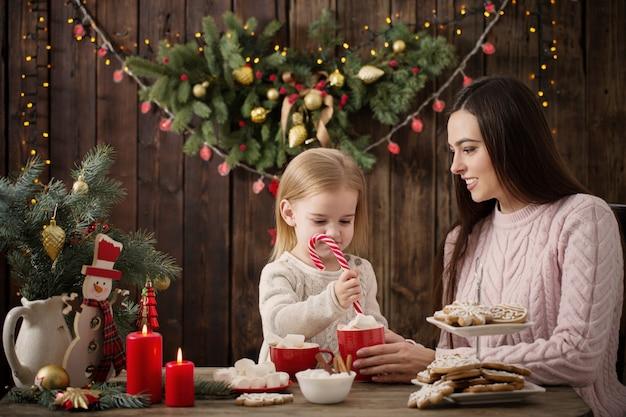 母と自宅のクリスマスクッキーを持つ少女