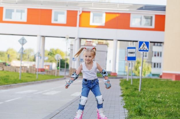 Маленькая девочка катается на роликовых коньках