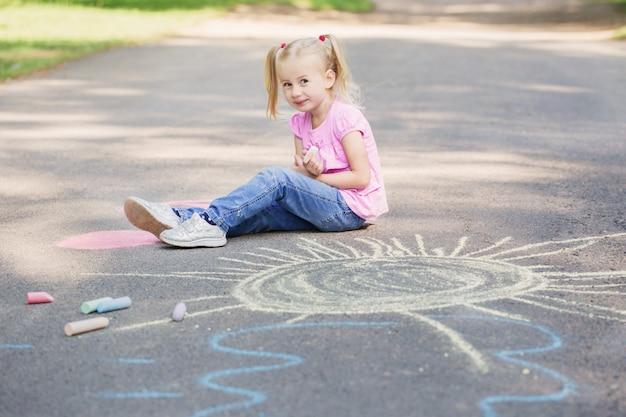 Маленькая девочка рисует мелом на асфальте