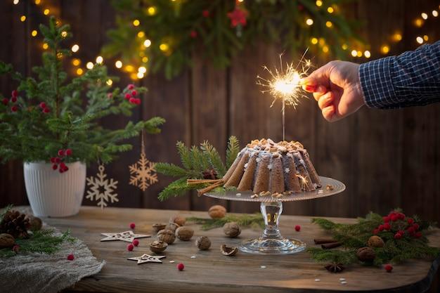 男性の手がクリスマスケーキに線香花火に火をつけた