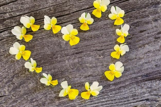 木製の背景にフォームハートの黄色い花