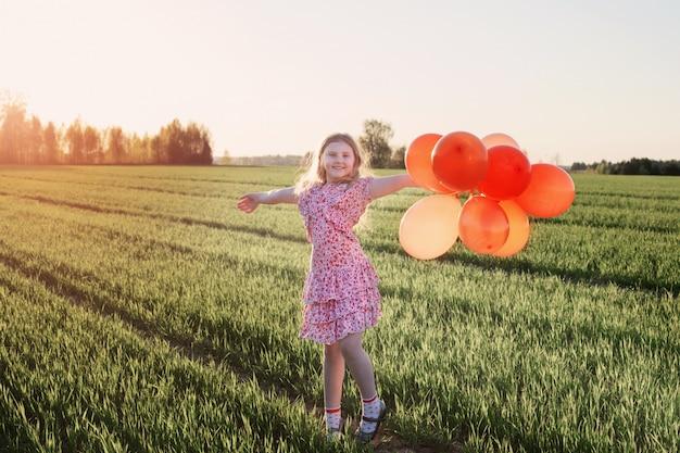 Счастливая девушка с оранжевыми воздушными шарами на открытом воздухе