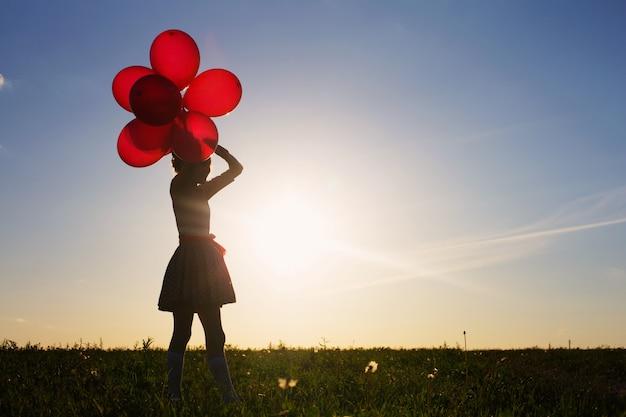 Счастливая девушка с красными воздушными шарами на открытом воздухе