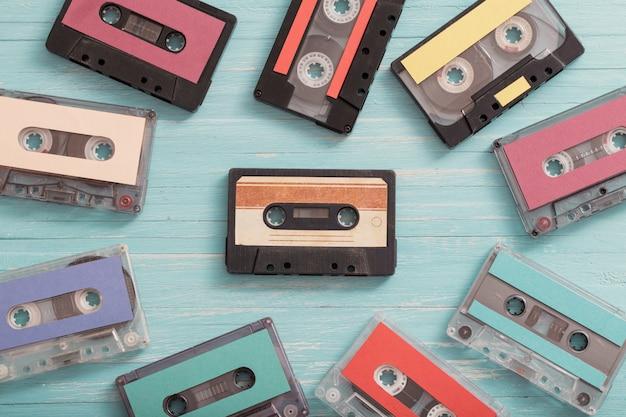木材の背景に古いプラスチックカセット。レトロな音楽のコンセプト