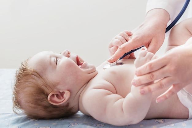 医師は聴診器で小さな子供に耳を傾けます