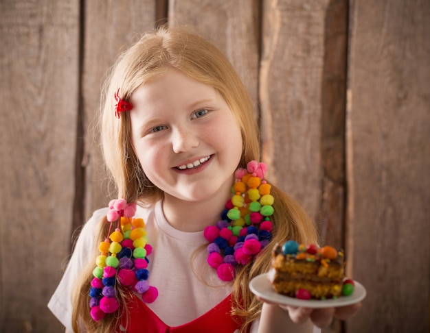 木製の背景にケーキと笑顔の女の子