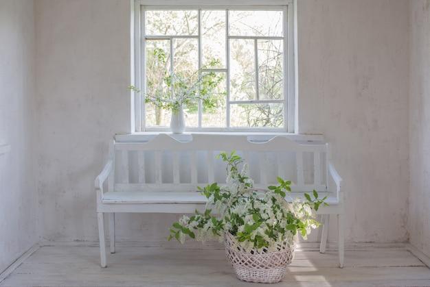 白い木製のベンチのバスケットの春の花