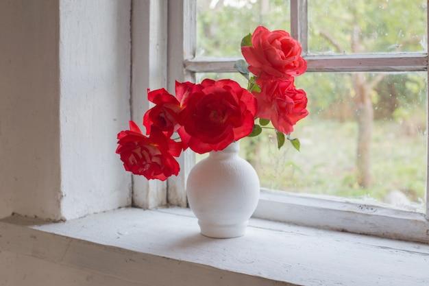 Красные розы на подоконнике