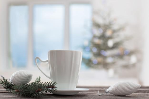 背景のクリスマスのモミとウィンドウの白いカップ