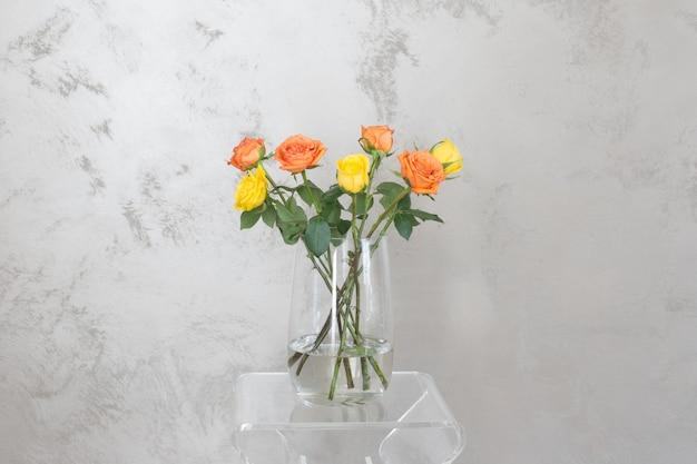 Желтые розы в стеклянной вазе