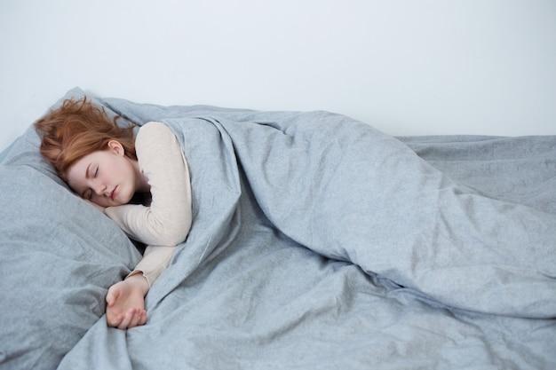 Девушка-подросток спит на кровати у себя дома