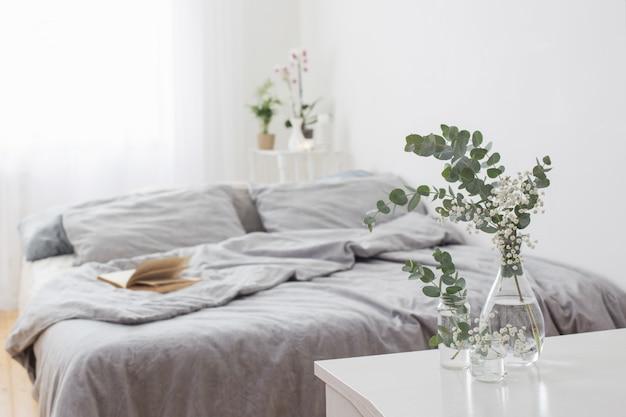 Эвкалипт в стеклянной вазе в белой спальне