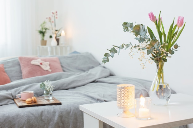 Интерьер спальни с цветами, свечами и чашкой чая