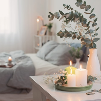 Горящие свечи и эвкалипт в вазе в белой спальне