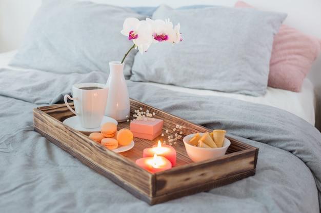 コーヒー、お菓子、キャンドル、花、ベッドの上の木製トレイにガート。バレンタインデーのコンセプト