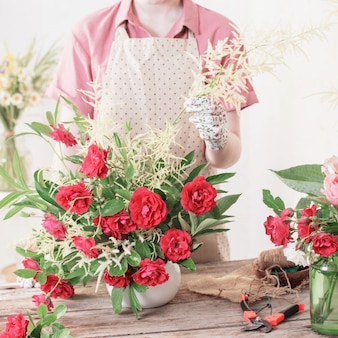 Девушка-флорист делает композицию из красных роз