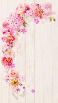 白い木製の背景にピンクの花