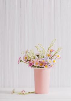 白い木製の壁の上に花瓶の春の花