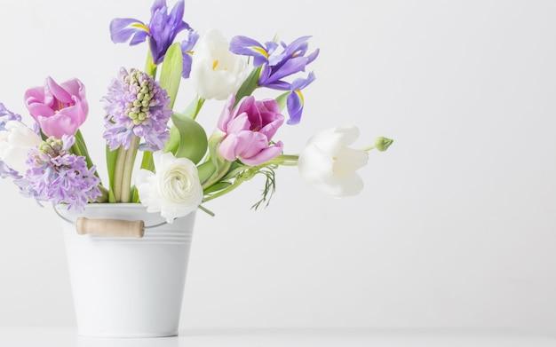 白い壁にバケツに春の花