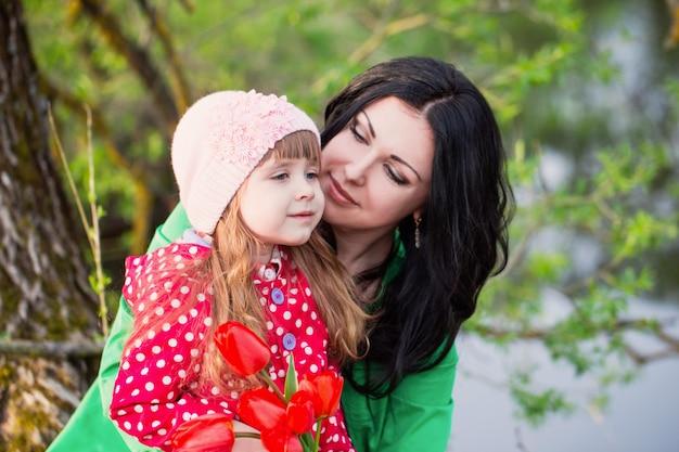 女性と花の花束を持つ子供