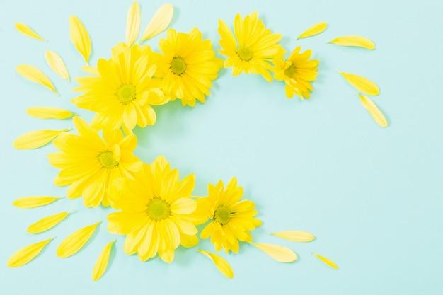 緑の紙の背景に黄色の菊