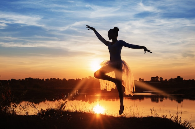 屋外で日没のバレエダンサーのシルエット
