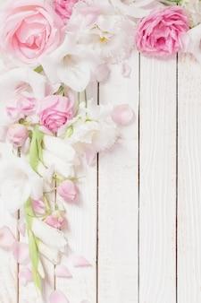 白い木製の背景にピンクと白の花