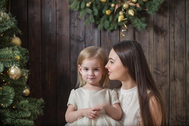 暗い木製のクリスマスツリーで母と娘