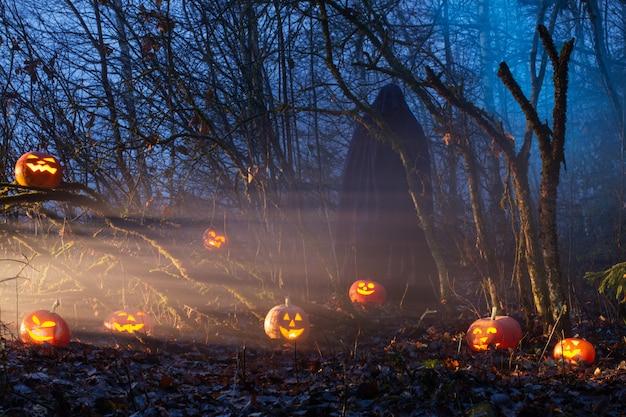 夜の森でハロウィンのカボチャと幽霊